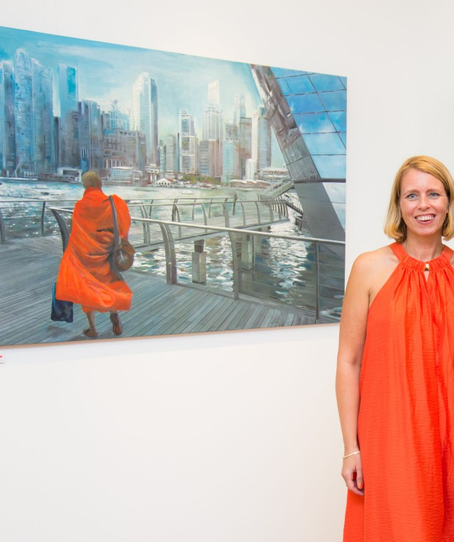 Artist Ingela Johansson with her monk painting at the exhibition Singapore Moments.